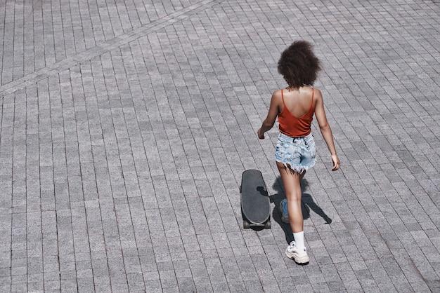 Junge frau im freien stil auf der straße, die in der nähe von skateboard geht