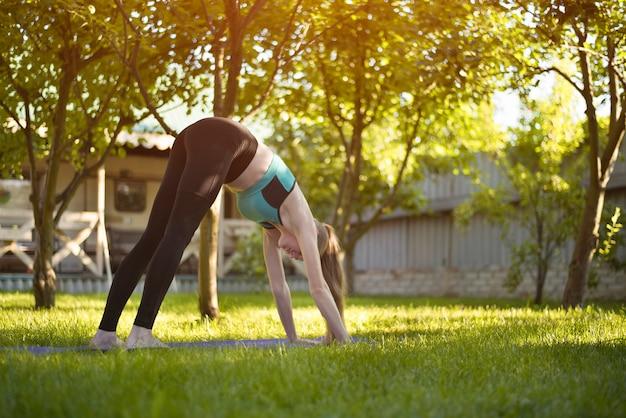 Junge frau im garten übt yoga.