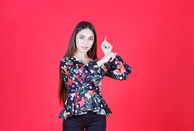 Junge frau im geblümten hemd, die auf roter wand steht und nach oben zeigt