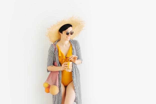 Junge frau im gelben badeanzug und strohhut mit netzbeutel mit früchten und cocktail.