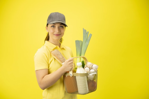 Junge frau im gelben einheitlichen handhabungskorb von lebensmitteln, obst, gemüse, milch und eiern