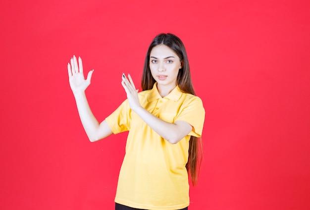Junge frau im gelben hemd, die auf roter wand steht und die größe eines gegenstandes zeigt