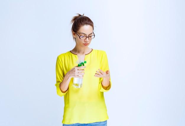Junge frau im gelben hemd, die ein reinigungsspray hält und es in der hand überprüft