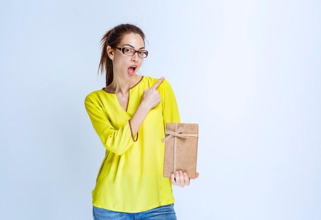 Junge frau im gelben hemd, die eine geschenkbox aus karton hält und auf jemanden rechts zeigt