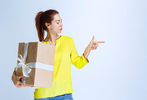 Junge frau im gelben hemd, die eine geschenkbox aus karton hält und auf jemanden zeigt