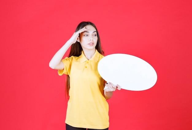 Junge frau im gelben hemd, die eine ovale infotafel hält und ihren kollegen neben sich einlädt