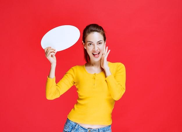 Junge frau im gelben hemd, die eine ovale infotafel hält und laut schreit