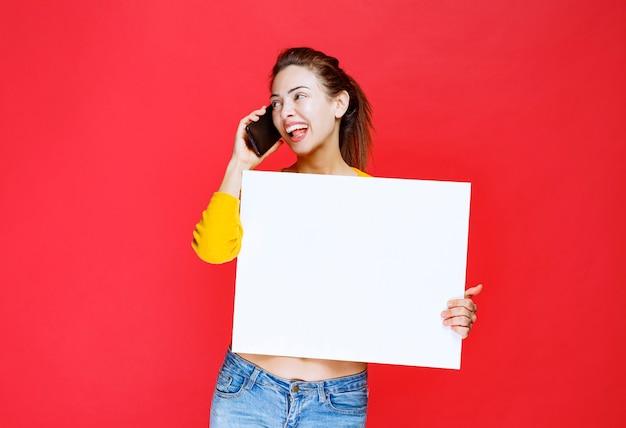 Junge frau im gelben hemd, die eine quadratische infotafel hält und mit dem telefon spricht
