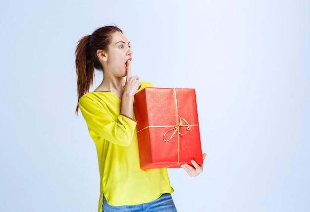Junge frau im gelben hemd, die eine rote geschenkbox hält und denkt oder zögert