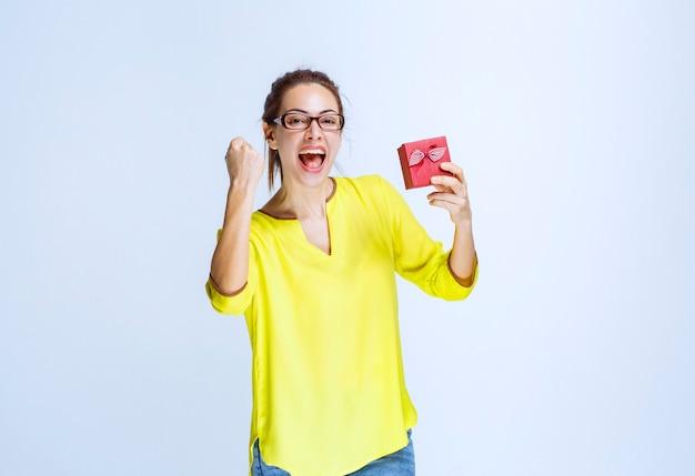 Junge frau im gelben hemd, die eine rote geschenkbox hält und freudenhandzeichen zeigt