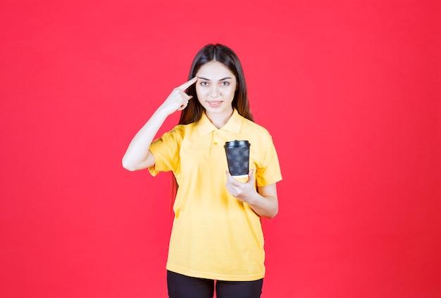 Junge frau im gelben hemd, die eine schwarze einweg-kaffeetasse hält, denkt und eine gute idee hat
