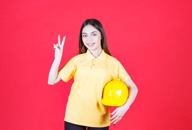 Junge frau im gelben hemd, die einen gelben helm hält und das produkt genießt