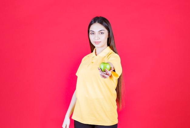 Junge frau im gelben hemd, die einen grünen apfel hält und dem kunden einen anbietet