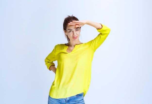 Junge frau im gelben hemd, die hand an die stirn legt und vorausschaut