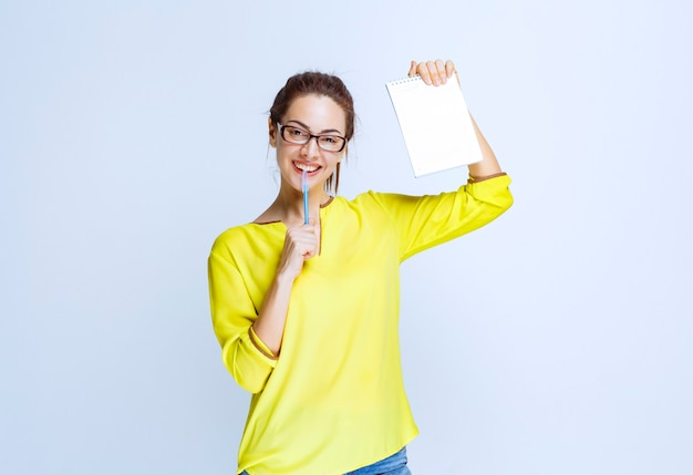Junge frau im gelben hemd, die ihr prüfungsblatt hält und denkt, während sie einen stift hält
