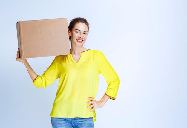 Junge frau im gelben hemd, die ihre pappfrachtkiste hält und sich glücklich fühlt