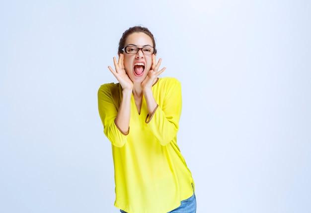 Junge frau im gelben hemd, die sich positiv fühlt und lacht