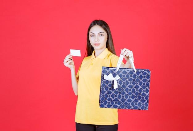 Junge frau im gelben hemd hält eine blaue einkaufstasche und präsentiert ihre visitenkarte