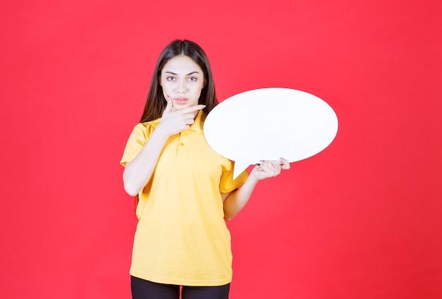 Junge frau im gelben hemd hält eine ovale infotafel und sieht verwirrt und nachdenklich aus