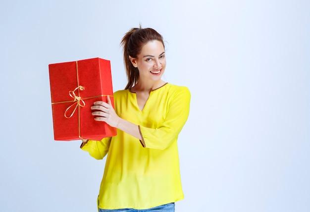 Junge frau im gelben hemd hält eine rote geschenkbox am valentinstag