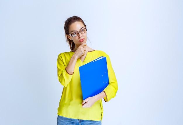 Junge frau im gelben hemd sieht nachdenklich und verträumt aus
