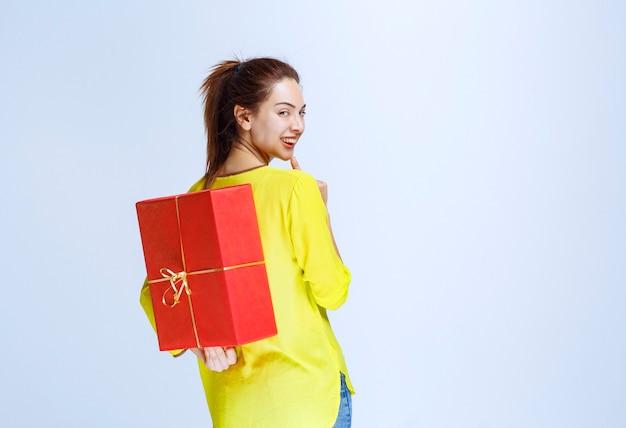 Junge frau im gelben hemd versteckt eine rote geschenkbox hinter sich
