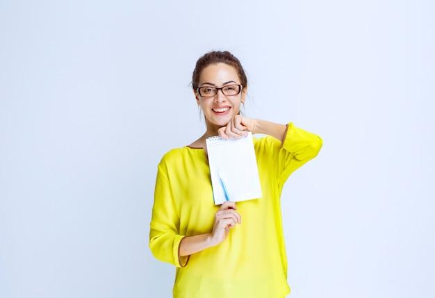 Junge frau im gelben hemd zeigt die quizergebnisse und die fehler darauf