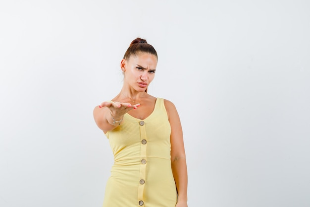 Junge frau im gelben kleid, das handfläche nach vorne erreicht und düster, vorderansicht schaut.