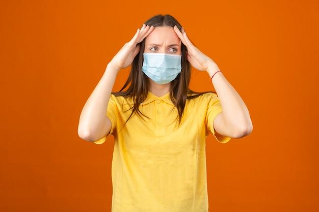 Junge frau im gelben poloshirt und in der medizinischen schutzmaske, die kopfgefühlkopfschmerz auf lokalisiertem orange hintergrund berührt