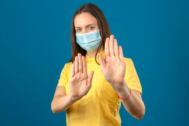 Junge frau im gelben poloshirt und in der medizinischen schutzmaske, die stoppgeste mit händen auf lokalisiertem blauem hintergrund machen
