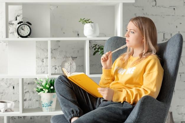 Junge frau im gelben pullover, graue hosen, die auf stuhl zu hause entspannen, nachdenklich nachdenklich aussehende schreibideen