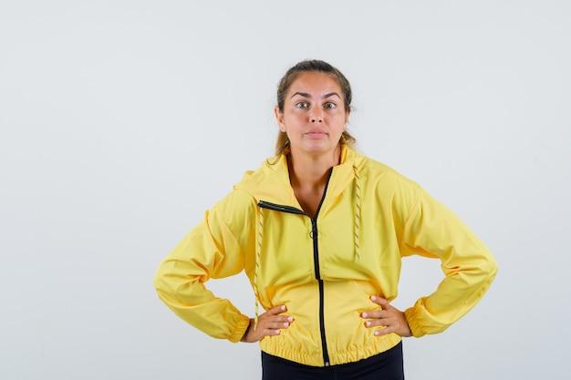 Junge frau im gelben regenmantel, der hände auf taille hält und konzentriert schaut
