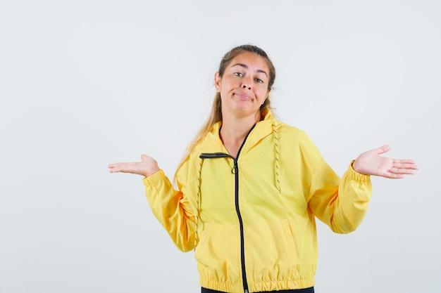 Junge frau im gelben regenmantel, der idk geste zeigt und eitel schaut