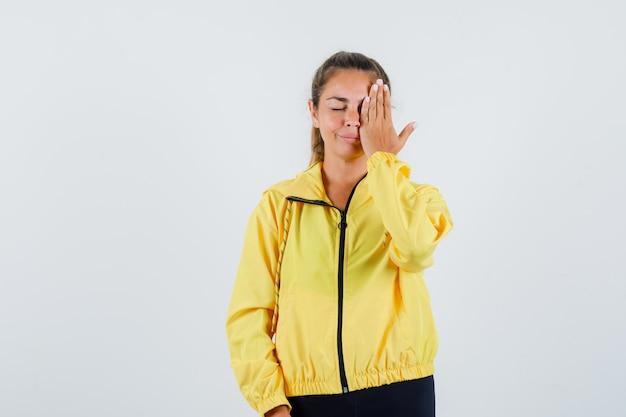 Junge frau im gelben regenmantel, der ihr linkes auge mit hand bedeckt