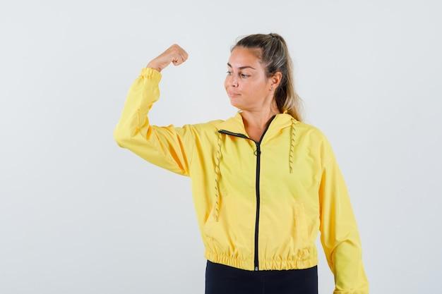 Junge frau im gelben regenmantel, der ihre armmuskeln zeigt und zuversichtlich schaut