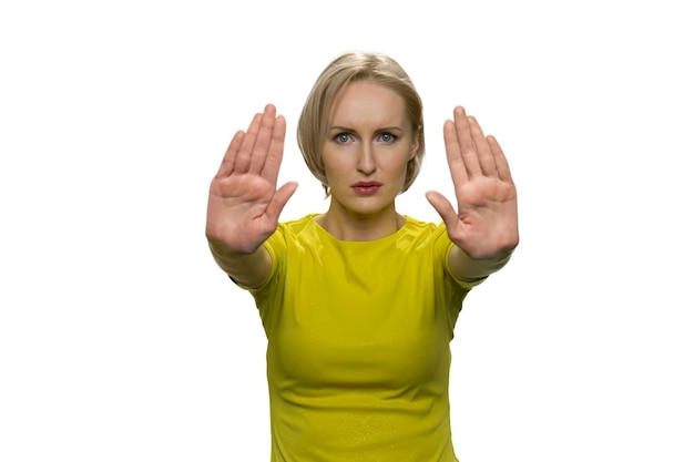 Junge frau im gelben rollkragenpullover, die mit beiden händen eine stoppgeste macht