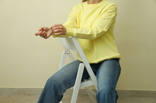 Junge frau im gelben sweatshirt, das gegen beige sitzt