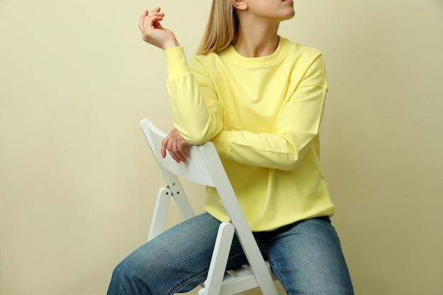 Junge frau im gelben sweatshirt, das gegen beigen hintergrund sitzt