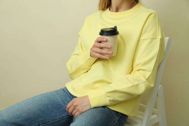 Junge frau im gelben sweatshirt, das mit pappbecher gegen beigen hintergrund sitzt