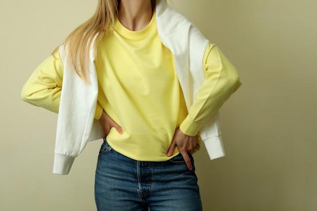 Junge frau im gelben sweatshirt gegen beigen hintergrund
