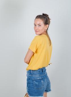 Junge frau im gelben t-shirt, jeans-shorts, die kamera mit malwerkzeugen betrachten.