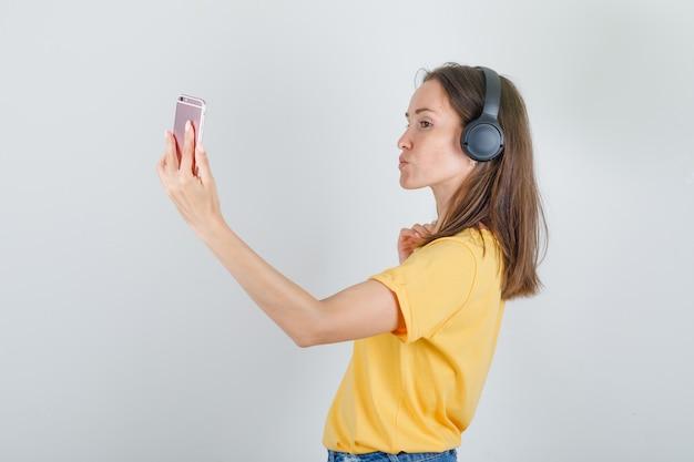 Junge frau im gelben t-shirt, shorts, die auf smartphone per videoanruf sprechen.
