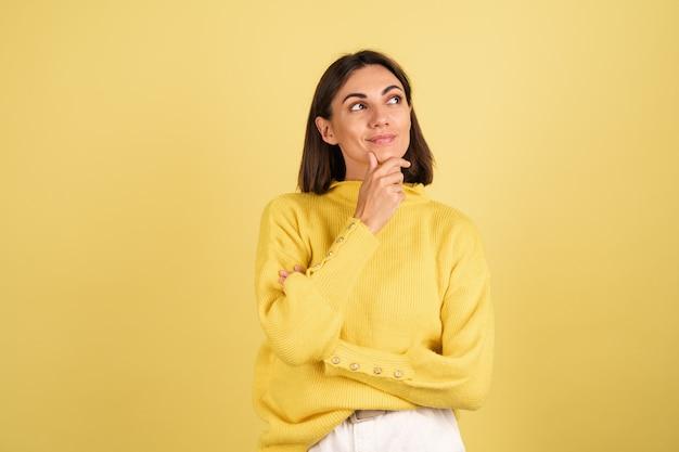 Junge frau im gelben warmen pullover, der ihr kinn berührt