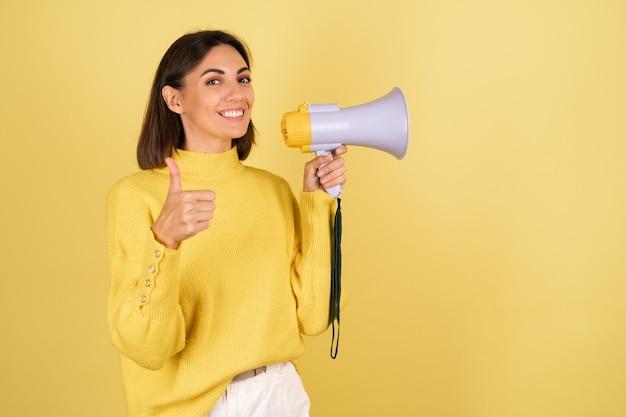 Junge frau im gelben warmen pullover mit megaphonlautsprecher, der daumen nach oben zeigt