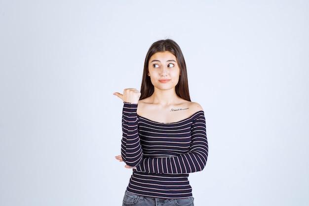 Junge frau im gestreiften hemd, das auf etwas hinter zeigt