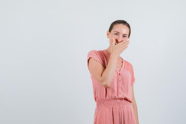 Junge frau im gestreiften kleid, das hand auf mund hält, während lachend, vorderansicht.