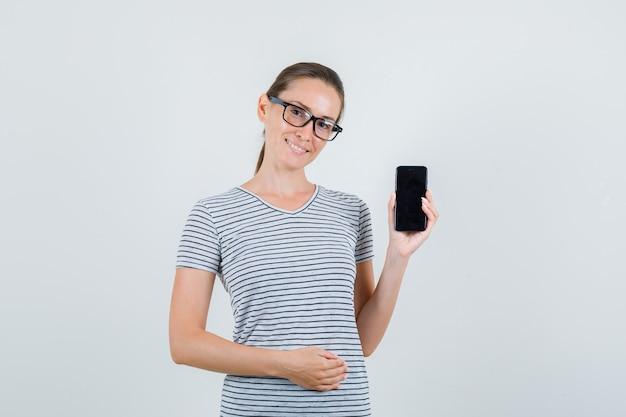 Junge frau im gestreiften t-shirt, brille, die handy hält und froh schaut, vorderansicht.