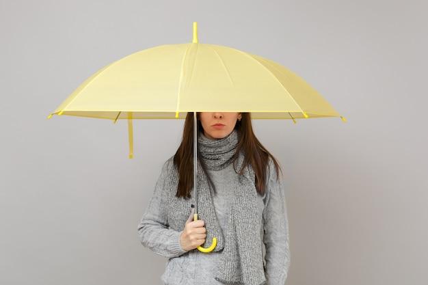 Junge frau im grauen pullover, schal, der gelben regenschirm hält und die augen bedeckt, die auf grauem wandhintergrund lokalisiert werden. gesunder modelebensstil, aufrichtige emotionen der menschen, konzept der kalten jahreszeit. kopieren sie platz.
