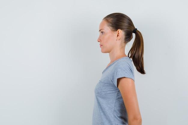 Junge frau im grauen t-shirt, das hände auf ihrem rücken hält und konzentriert schaut.