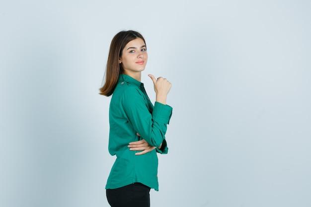 Junge frau im grünen hemd, das daumen oben zeigt und erfreut schaut.